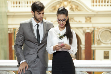 businessman and business woman reading text message
