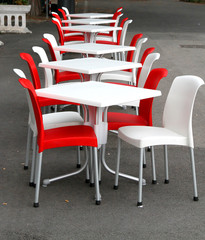 Red and white chairs with tables in an outdoor café on the road