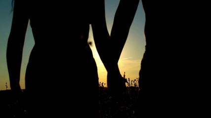 Man and woman in a field at sunset.Couple in love at sunset.