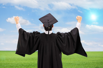 Male graduate gesturing happiness in an open field