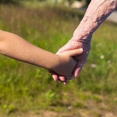 Hands of old woman and child.