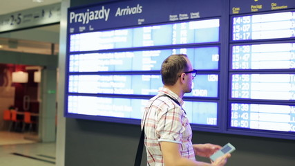 Young man checking departure timetable board at train station