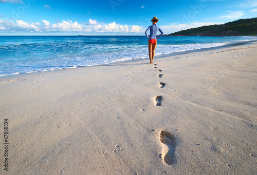 Woman at beautiful beach. Focus on footprints.