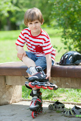 The child put on roller skates on a bench in the summer Park