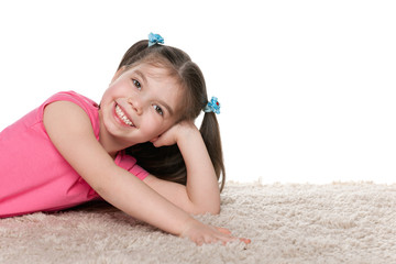Happy little girl on the white carpet