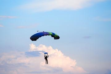 unidentified skydiver, parachutist on blue sky