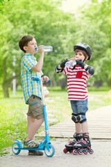 Children with scooter and rollers drink water