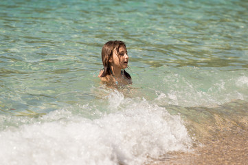 Young Girl Playing on Waves In The Sea on Summer Holiday