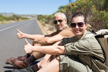 Hitch hiking couple sitting on the side of the road smiling at c