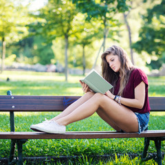 Young woman reading a book under a tree in the park. Filtered im