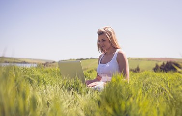 Pretty blonde sitting on grass using her laptop