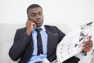 Businessman making a call while reading the paper on sofa
