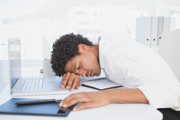 Exhausted businessman sleeping at his desk