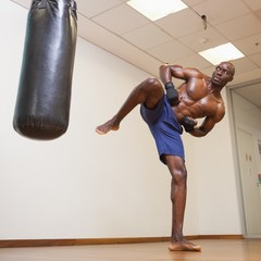 Muscular boxer kicking punching bag in gym