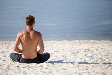 Sitting man doing yoga on shore of ocean
