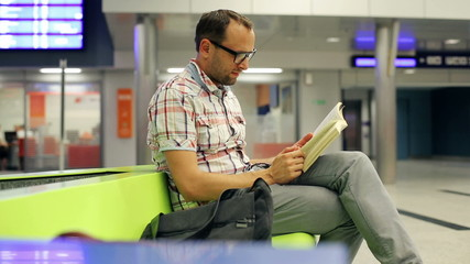Young man reading book, waiting at train station