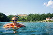 Young kid swimming in Lavarone lake with life buoy. Trentino Alt