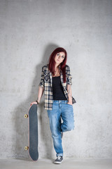 Woman with skateboard full body portrait against concrete wall.