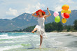 Young woman playing on the beach with colorful balloons