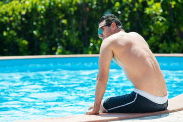 Handsome man portrait in swimming pool.