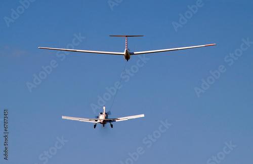 Leinwanddruck Bild airplane towing a glider