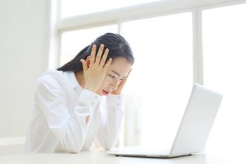パソコンを前に困る若い女性