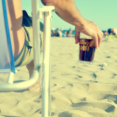 young man with a glass with cola drink on the beach, with a filt