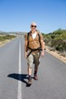 Handsome hiker walking on road and smiling at camera