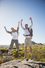 Hiking couple jumping and cheering on rocky terrain