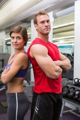 Fit attractive couple smiling at camera with arms crossed
