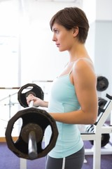 Fit brunette holding heavy barbell