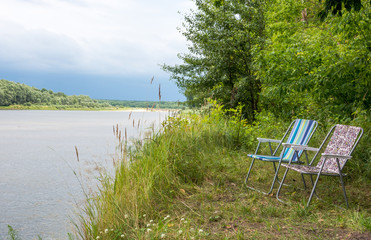 Two folding chairs on nature, on the banks of the river