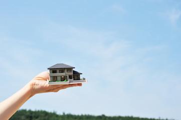 手にもっている住宅模型と青空