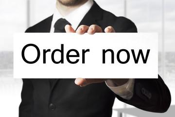 businessman holding sign order now