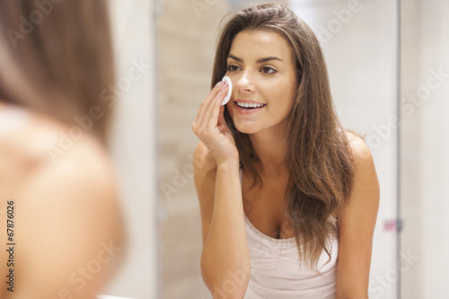 Beautiful brunette woman removing makeup from her face - 67876026