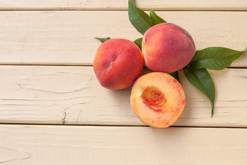 Fresh organic peaches on a yellow rustic table - top view
