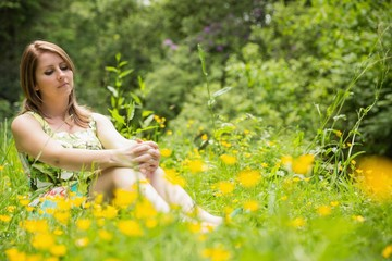 Cute young woman relaxing in field