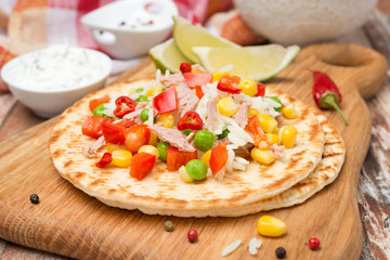 colorful vegetable salad with tuna on wheat tortillas, close-up