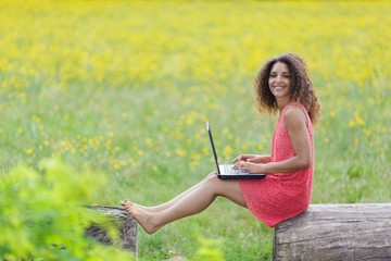Young woman using laptop in nature