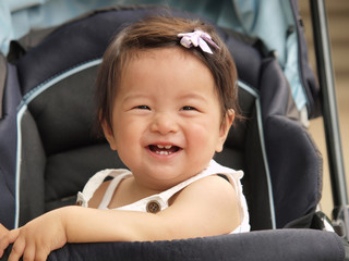ベビーカーに乗って笑う女の子