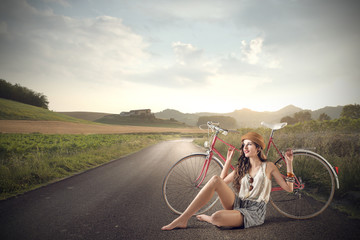 beautiful girl sitting on the road with her bike