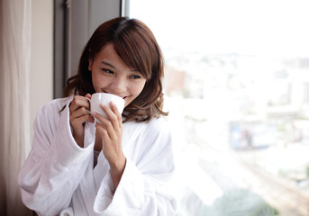 attractive woman holding a cup of coffee, smiling.