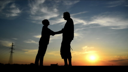Man meeting woman on the street in sunset and greeting her