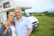 Happy senior couple standing in front of camping car - 67881208