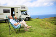 Senior couple relaxing in camping folding chairs, sea landscape - 67881218