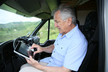 Senior man in camper using digital tablet