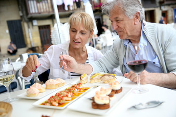 Senior couple eating Spanish fingerfood in Spain
