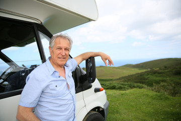 Senior man standing by camper, scenery in background