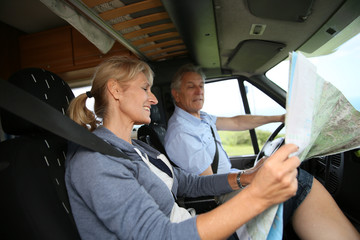 Senior couple riding camper and reading road map