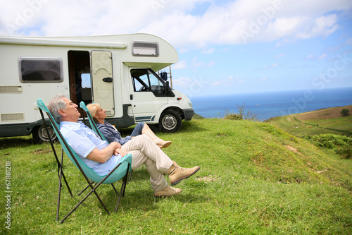 Leinwanddruck Bild Senior couple relaxing in camping folding chairs, sea landscape